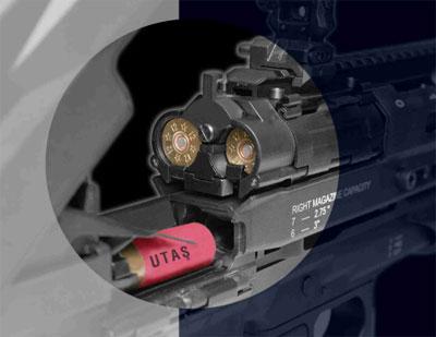 Вид на казенную часть ствола и магазины ружья UTAS UTS-15. Крышка ствольной коробки открыта, затвор в заднем положении. Хорошо видна качающаяся направляющая, контролирующая подачу патронов из магазинов на линию подачи в ствол, а также переключатель магазинов, находящийся в среднем положении (подача поочередно из обоих магазинов).