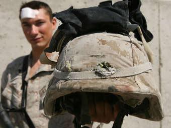 Американский солдат демонстрирует задержавший пулю кевларовый шлем
