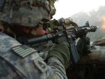 Американский солдат ведет огонь из автомата M4