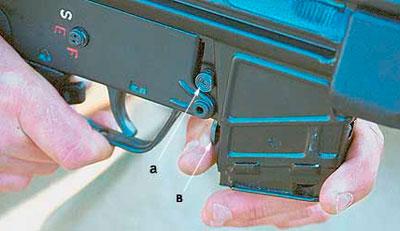 Штатная кнопка защелки магазина (а) находится с правой стороны винтовки над магазином, а дополнительная кнопка (в) находится перед спусковой скобой
