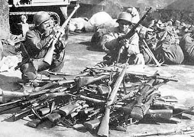 Американские солдаты разряжают трофейное германское стрелковое оружие, представлявшее собой арсенал практически всех оккупированных стран. На переднем плане лежит 7,35-мм итальянская винтовка Маннлихер-Каркано М 1938, получившая в вермахте индекс «Gewehr 231(i)».