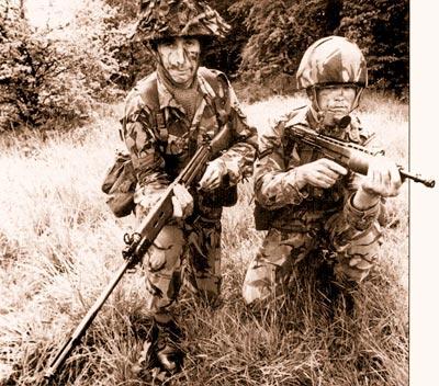 Старая винтовка L1A1 калибра 7,62x51 мм (слева) и новая SA80 калибра 4,85 мм, представленные вместе на рекламном армейском фотоснимке в 1976 г. Хотя и широкоугольный объектив искажает размеры L1A1, очевидно, что схема «буллпап» компактнее и удобнее в обращении