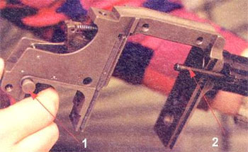 Ударно-спусковой механизм «Протекты» - самовзводный, курковый. Хорошо видна боевая пружина, работающая на растяжение. Стрелками указаны: 1 - кнопочный предохранитель, 2 - экстрактор