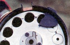 Шторка, препятствующая выпадению патрона из патронника. При провороте барабана шторка автоматически открывается