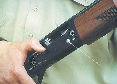 Стрелкой на фото показана кнопка затворной задержки. Флажок отсекателя располагается на левой стороне ствольной коробки