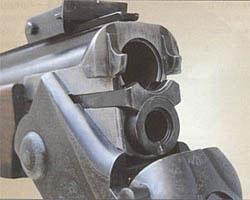 В области казенного среза верхнего ствола по обе стороны от патронника выполнены так называемые клыки, которые при закрывании стволов входят в соответствующие пазы щитка колодки и подпираются защелкой, являясь дополнительными (вспомогательными) элементами системы запирания ружья. Основным элементом запирания является клиновидная рамка, входящая в фигурный паз, расположенный в нижней торцевой части ствольной муфты
