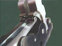 Фрагмент замков. Верхние плечи боевых пружин разжимаясь воздействуют на тыльную сторону курков через микроподшипник. При этом плечо действия силы пружины увеличивается