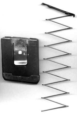 Четырехместный магазин со снятой пружиной от магазина Сайги-20. 1 - зацеп на пружинящей пластине, его-то и нужно снизу выводить немного на острый внутренний угол. На фото пружина от 5-местного магазина от Сайги 20-к - с откушенным нижним рамочным опорным витком. Форму рукояти затвора можно изменить, сделав на конце рукояти традиционный для винтовок шарик. Это повысит удобство перезарядки, но увеличит поперечные габариты. Так что делать его или нет - решать владельцу самостоятельно.