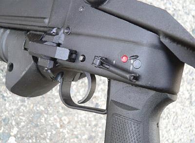 Собеих сторон ствольной коробки магазинного гранатомета ГМ-94 над пистолетной рукояткой управления огнем смонтирован флажковый предохранитель
