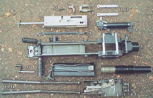 Детали частичной разборки гранатомёта АГС-17 «Пламя»: 1 - короб (лоток не снят), 2 - ствол, 3 - приёмник, 4 - УСМ, 5 - механизм перезарядки, 6 - спусковая планка, 7 - затвор, 8 - досылатель, 9 - боевая плита, 10 - ударник, 11, 12 - рычаги затвора, 13, 14 - возвратные пружины, 15 - ось затыльника