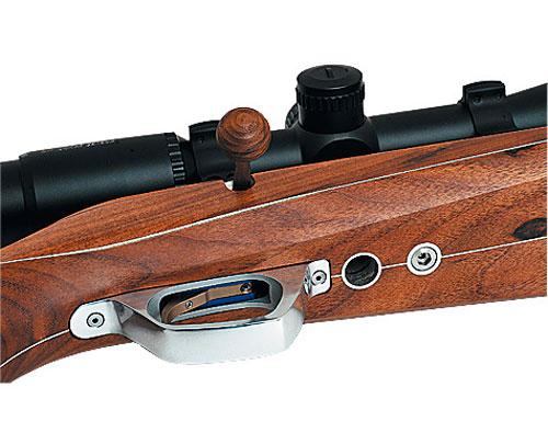 Нижнее окно для выброса стреляной гильзы в ложе спортивной винтовки. Под ней — охотничья винтовка со съемным магазином.