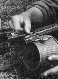 Заряжание единого пулемета MG.34 металлической патронной лентой с незамкнутыми звеньями Gurt 34