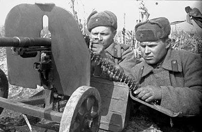 Советский пулеметный расчет ведет стрельбу из станкового пулемета Горюнова СГ-43. Второй номер расчета поддерживает металлическую патронную ленту