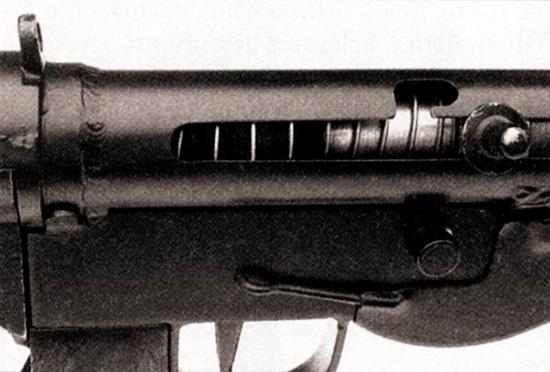 Правая сторона ствольной коробки и спускового механизма «Стэн» Mark V. Видны прорезь для рукоятки взведения и предохранительный паз, а также переключатель режимов огня, расположенный непосредственно под рукояткой взведения