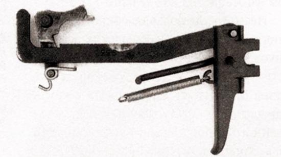 Детали спускового механизма «Стэн», расположенные так, как они установлены в корпусе, за исключением пружины спускового крючка, которая соединяется с нижним крючком на пружине шептала. Обратите внимание на изношенное покрытие в верхней части спусковой тяги, здесь располагается переключатель режима огня (на фото отсутствует)