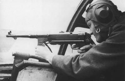 Пилот германского самолета-бомбардировщика ведет стрельбу из пистолета-пулемета МР.40