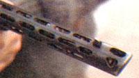 Скошенный передний срез кожуха ствола и три фигурных отверстия в нём выолняют роль дульного тормоза компенсатора (по типу ППШ)