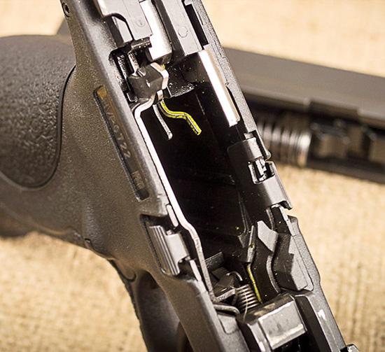 Рычаг безопасности при извлеченном магазине (стальной) и рычаг блокировки затвора (желтого цвета) пистолета M&P9