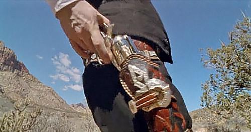 Начало движения. Револьвер еще в кобуре, но большой палец уже лег на курок, а рука подалась вверх.