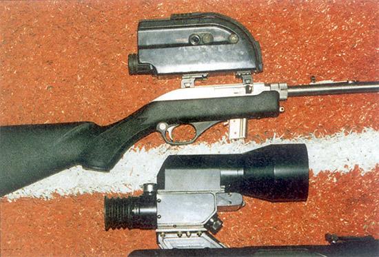 Модернизированный прицел ПОНД-4, установленный на снайперской винтовке  СВД (внизу), и ночной прицел ПОН-3 для охотников, установленный на  самозарядной малокалиберной винтовке «Marlin». В затемненном тире из-за  отвратительной регулировки пристрелять ПОН-3 так и не удалось,  следовательно, не удалось оценить и его возможности, хотя картинка  выглядела достаточно ясной и четкой. Заслуживает внимания модификация  ПОНД-4, на которой устранены недостатки, выявленные на «Выстреле».  Наконец-то сошлись прицельные марки дневного и ночного каналов, и  вводить поправку при переключении не нужно. Кронштейн стал заметно  жестче, что позволило установить прицел на СВД. Все электрические цепи  выключателей сведены на один четырехпозиционный (его ручка видна на  передней поверхности корпуса прицела), что повысило удобство  эксплуатации. Однако ПОНД-4 не стал доступнее для армейских снайперов.