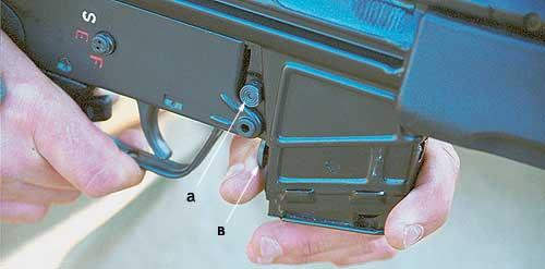 Штатная кнопка (а) базовой НК33 находится с правой стороны винтовки над магазином. Дополнительная кнопка (в), находящаяся перед спусковой скобой, позволяет оперативно отсоединять и присоединять магазин левой рукой, не меняя изготовки и не снимая правую с рукоятки удержания оружия