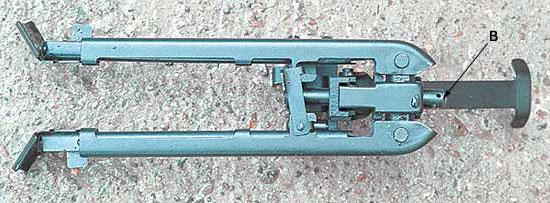 Так выглядит сложенная «ижмашевская» сошка, отделённая от винтовки. а - шина, подпирающая цевье снизу; в - винт, с помощью которого регулируется усилие, с которым шина давит на цевье